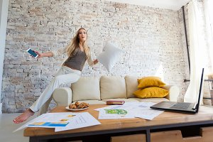 cheerful beautiful girl jumps on a sofa. Freelancer, computer.