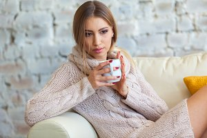 Beautiful woman holding a cup of coffee in her hands. in a knitted beige sweater.