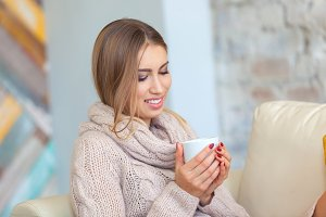Beautiful woman holding a cup of coffee in her hands. in a knitted beige sweater