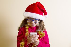 girl wirh santa hat and mobile phone