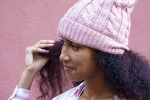 girl with wool hat on pink backgroun