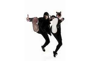 The silhouettes of two hip hop male and female break dancers dancing on white background