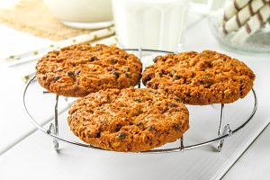 Homemade oatmeal cookies. Cookies on an iron grate on a wooden white table.
