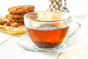 Homemade oatmeal cookies and tea on a wooden white table.