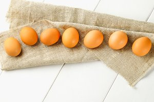 Raw brown chicken eggs in one row on burlap on a white wooden table. Ingredients for cooking.