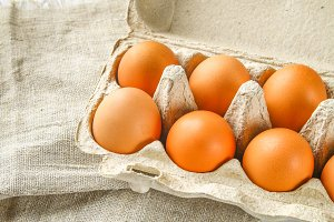 Raw brown chicken eggs in a cardboard tray with cells on sacking on a white wooden table. Ingredients for cooking.