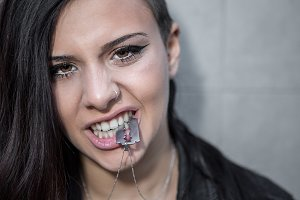Woman with razor necklace in mouth
