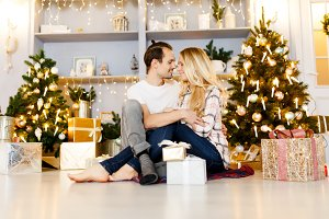 Sweet couple opening Christmas gifts