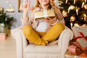 Picture of girl sitting in chair on background of Christmas decorations