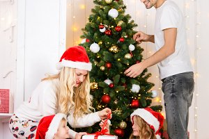 Happy family decorates Christmas pine