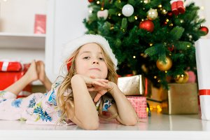 Image of girl in Santa cap lying on floor
