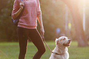 Image of beautiful woman on walk with dog in summer park