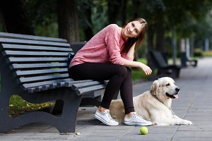 Image of smiling girl sitting on bench, dog retriever