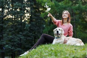 Image from below of woman pointing forward next to dog on green lawn
