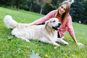 Photo of brunette hugging retriever on lawn