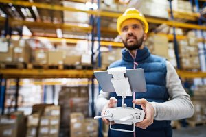 Man with tablet and drone controller in a warehouse.