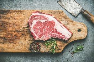 Raw beef steak rib-eye on board with seasoning and knife