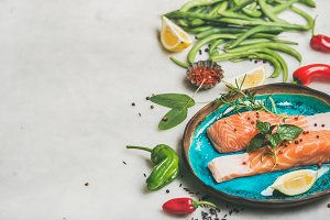 Raw salmon steaks with vegetables, greens, rice in blue plate