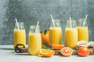 Healthy yellow smoothie with citrus fruit on wooden board
