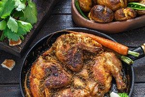 Whole roast chicken in an iron pan on dark background