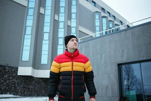 Handsome young man outdoor in colorful winter jacket looking away at cold gray urban background