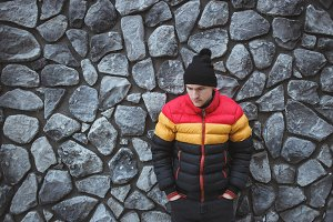 Handsome young man wearing colorful winter jacket and winter hat standing at stone gray wall outdoors. Winter time