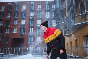 Strong man with in winter clothes enjoys the snow, cold, snowfall, blizzard. Urban yard background