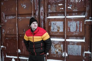 Winter look of strong man. Male wearing in red yellow black colored down jacket. Industrial background