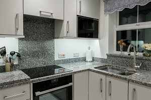 Small modern kitchen in apartment with granite worktop