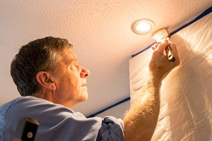 Senior adult man painting ceiling of kitchen