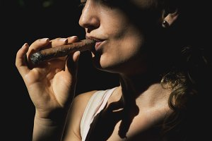 Beautiful woman smoking a cigar.