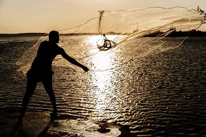 Unrecognizable fisherman using a net