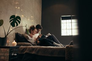 Couple on bed reading book