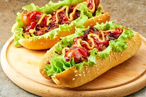 Two homemade hot dogs with lettuce, bacon and onion toppings