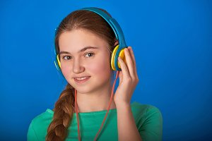 Teen girl loves to listen to the song with headphones.close-up portrait of a girl teenager in the headphones