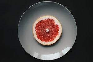 Single slice of pomelo on gray plate