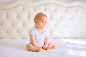sad baby in white sunny bedroom