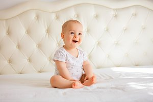 ovely baby boy in white sunny bedroo