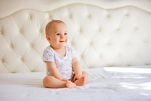 handsome baby boy in white sunny bed