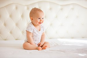Adorable baby boy in white sunny bed