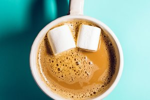 Coffee with milk and eyes of marshmallow for an invigorating mood. hot drink. view from above. turquoise background