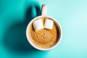 a mug of hot coffee with milk. Chewing marshmallows in coffee in the form of eyes. view from above. the background is turquoise.