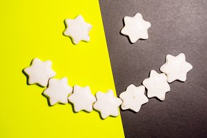 smile from a cookie. cookies in the form of stars. background is yellow-black. view from above