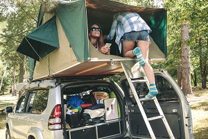 Woman walking up ladder to tent over car