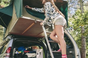 Woman standing in ladder opening tent over car