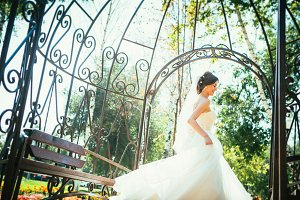 Young beautiful bride standing in a park gazebo.