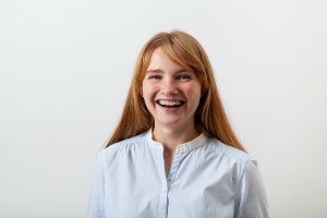 Studio portrait of pretty red-headed lady dressed in casual blue shirt