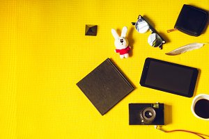 vacation and travel. soft toy, coffee, camera, pen, black notepad for notes. view from above