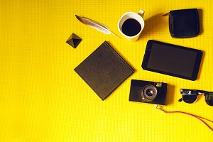camera while on vacation. notepad, purse, glasses, tablet. yellow background. view from above
