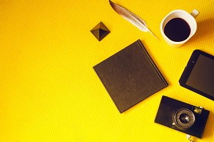 black objects. camera, notebook, coffee, tablet. view from above
